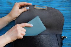 The girl hand takes out a gray purse from a black leather bag. Woman hand is laying a gray notebook in a black leather bag royalty free stock photo