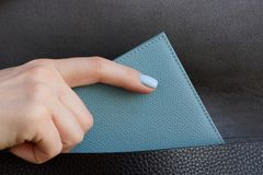 The girl hand takes out a gray purse from a black leather bag. Woman hand is laying a gray notebook in a black leather bag royalty free stock image