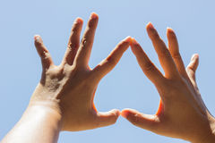 Girl hand in upside down heart form love blue sky Royalty Free Stock Photo