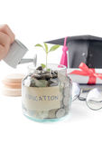 Girl hand watering a tree growing out of silver coins Stock Photos