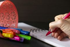 Girl hand writing on notebook with red pen and a basket with color pens. Dark table and background royalty free stock images