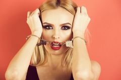 Girl with handcuffs, blonde woman with red lips. Girl with handcuffs, fashion blonde young woman with fashionable makeup, red lips and blonde hair stock image
