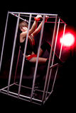 Girl in handcuffs sitting in cage in red light Stock Photos