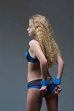 Girl in handcuffs standing back. visible ass Royalty Free Stock Image
