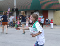 Girl handing out candy in a  parade in small town America Royalty Free Stock Images
