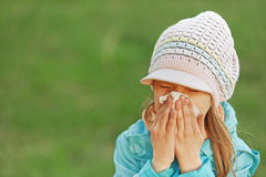 Girl with handkerchief. Little girl in blue coat with handkerchief sneezes Royalty Free Stock Photography