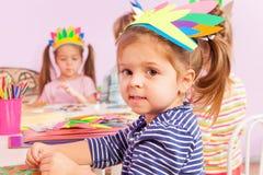 Girl in handmade headwear glue paper to cardboard Royalty Free Stock Photos