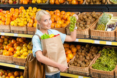 Girl hands bag with fresh vegetables choosing grape Stock Photo