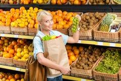 Girl hands bag with fresh vegetables choosing grape Stock Photo