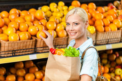 Girl hands bag with fresh vegetables choosing oranges Stock Photography