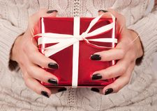 Girl hands with black nail and sweater holds red gift box. Young Female holding red gift box with white tie bow in hands with black finger nails and sweater Royalty Free Stock Images