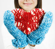 Girl hands in blue knitted mittens holding romantic red heart - Stock Photography