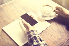 Girl hands with cappuccino, cell phone and blank diary. Vintage photo effect royalty free stock photography