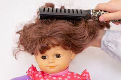 Girl hands combing hair of female doll stock image