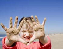 Girl with hands covered with sand Stock Photography