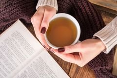 Girl hands with cup of tea and open book on wooden desk. Young beautiful woman hands with cup of tea and open book on wooden desk. Woman wears wool sweater stock image