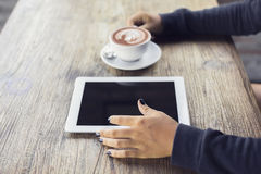 Girl hands, digital tablet and coffee on a wooden table Royalty Free Stock Images