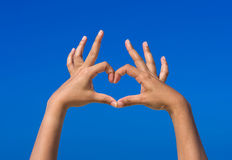 Girl hands forming be heart for love with blue sky Royalty Free Stock Image