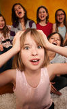 Girl with Hands on Head. Little Caucasian girl with hands on head while friends laugh Stock Photography