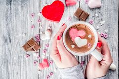 Girl hands hold hot chocolate with marshmallow hearts royalty free stock photos