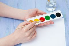 The girl hands hold watercolors and paintbrush for drawing. Close-up stock photography