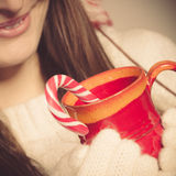 Girl hands holding mug and cane. Royalty Free Stock Photo