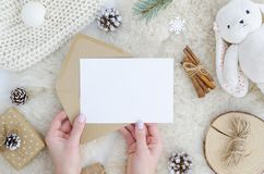 Girl hands holds blank paper mock up with space for text, art work,lettering, pine cone fir branch,rope,rabbit toy on. Fur background. Flat lay, top view. Cosy stock photography