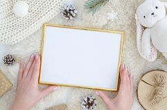 Girl hands holds gold photo frame mock up with space for text, art work,lettering, pine cone fir branch,rope,rabbit toy. Girl hands holds blank paper mock up stock photo