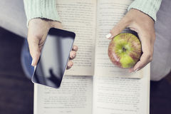 Girl hands keeping smartphone, apple and open books Royalty Free Stock Photo