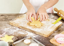 Girl hands making heart shaped cookie Royalty Free Stock Images