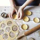 Girl hands making shortcrust pastry for little tart on molds on rustic background with rolling pin and flour Stock Photos