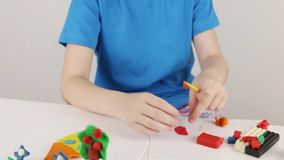 Girl hands molding house, tree, flowers from plasticine on table. In white room stock video footage