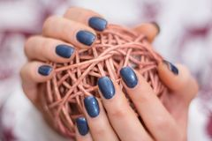 Girl hands with navy blue manicure holding decorative hank. Young girl hands with navy blue manicure holding decorative hank. Winter manicure color and royalty free stock photo