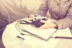 Girl hands with old style camera and books outdoor Royalty Free Stock Photography
