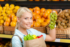 Girl hands packet with fresh vegetables choosing grape Stock Photography
