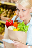 Girl hands packet with fresh vegetables reading list of products Stock Photo
