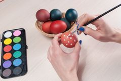 Girl hands painting Easter eggs with brush on wooden table stock image