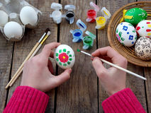 The girl hands painting eggs with floral patterns gouache. Decorating egg. Preparation for Easter. Royalty Free Stock Image