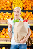 Girl hands paper bag with fresh vegetables reading list of products stock image
