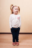 Girl With Hands in Pockets. Little girl with hands in pockets and side gaze, posing in studio Royalty Free Stock Images