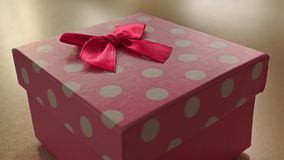 Girl hands with red manicure place pink and white polka dot gift box on table stock video footage