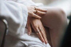 Girl hands in rings on the legs. Stock Photography
