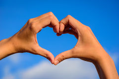 Girl hands in shape of love heart on blue sky Royalty Free Stock Photos