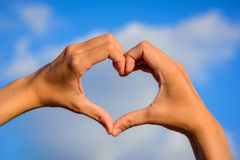 Girl hands in shape of love heart on blue sky Stock Photography