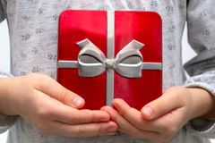 Girl hands showing the gift in a box, holding red Gift box with bow over holiday background royalty free stock images