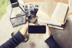 Girl hands with smartphone, old camera and books royalty free stock photography