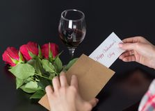 Girl hands takes a message Happy Valentines Day on paper from the retro envelope on black desk with red rose bouquet and red wine royalty free stock photography