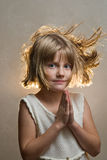 Girl with hands together. Girl holds her hands together back light with hair blowing Royalty Free Stock Photos