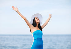 Girl with hands up on the beach Stock Photo