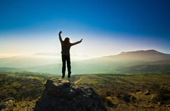 Girl with hands up in the mountains against sun Royalty Free Stock Photo